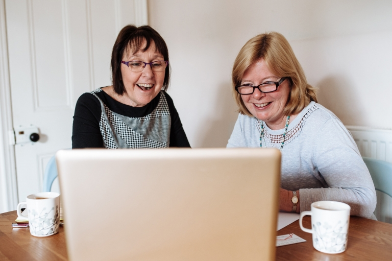 two ladies laughing over a laptop